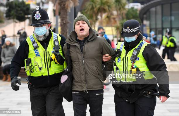 Police arrest a protester on the seafront on January 09, 2021 in Bournemouth, England. Chief Medical Officer Chris Whitty has filmed an advert for HM...