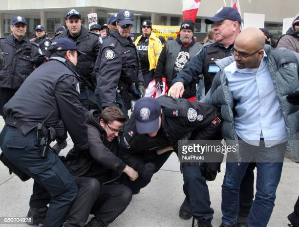 Police arrest a protestor during a counterprotest against Islamophobia and Fascism in downtown Toronto Ontario Canada on March 19 2017 Protesters...