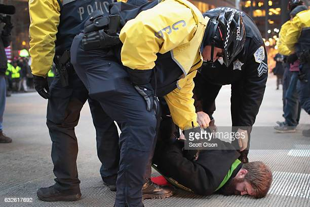 Police arrest a protestor who was sitting in the street blocking traffic demonstrating against President Donald Trump during the evening rush hour in...