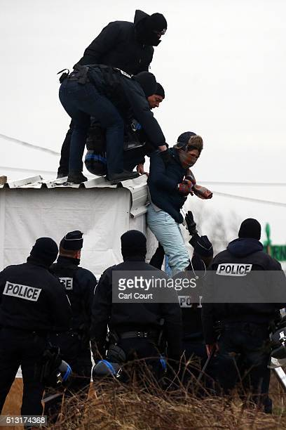 Police arrest a woman who had threatened to cut her wrist as she was removed from the roof of a hut as they cleared the 'jungle' migrant camp on...