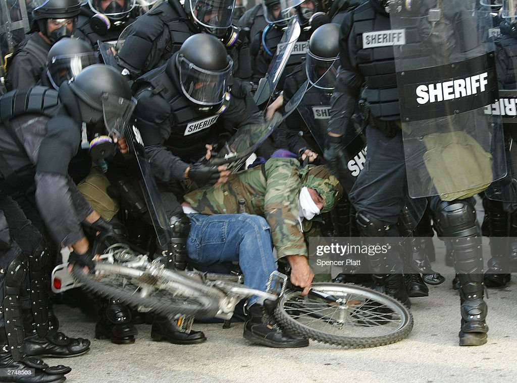 Police arrest an anti-globalization protester during clashes on the fourth day of the summit to create a Free Trade Area of the Americas November 20, 2003 in Miami, Florida. Hundreds of protesters, including a group of anarchists, clashed with police throughout the morning as they unsuccessfully tried to make their way to the Hotel Inter-Continental where the summit was taking place. Protesters say the pact would damage the environment, exploit workers overseas and cost many Americans their jobs.