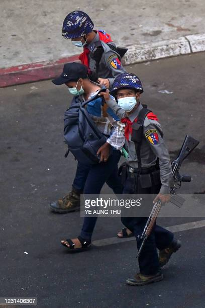 Police arrest Myanmar Now journalist Kay Zon Nwe in Yangon on February 27 as protesters were taking part in a demonstration against the military coup.