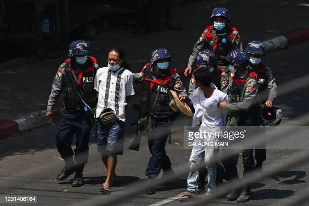 Police arrest people in Yangon on February 27 as protesters were taking part in a demonstration against the military coup.