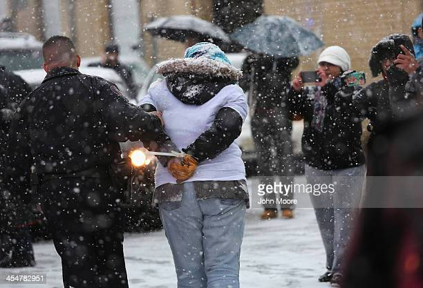 Police arrest protesters who had chained themselves together to block the entrance of an immigrant detention center on December 10 2013 in Elizabeth...