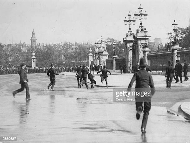 Police arrest Suffragettes who are chaining themselves to the railings outside Buckingham Palace London