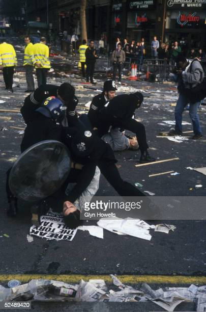 Police arresting demonstrators as a photographer takes pictures at the Poll Tax riot in Trafalgar Square London 31st March 1990