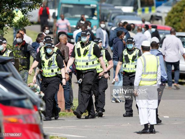 Police arrive to disperse mourners due to the Covid-19 restrictions of only 20 people allowed at the graveside at the cemetery during the funeral of...
