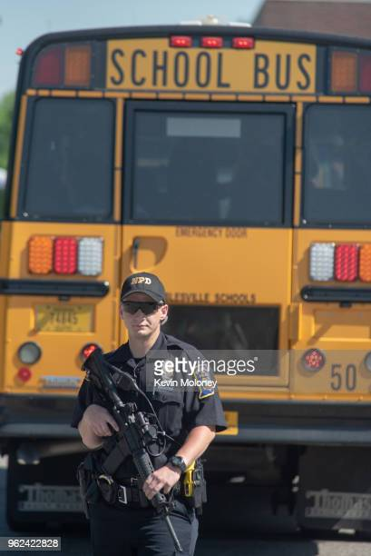 Police asses the scene outside Noblesville High School as evacuated middle school students wait on a bus after a shooting at Noblesville West Middle...