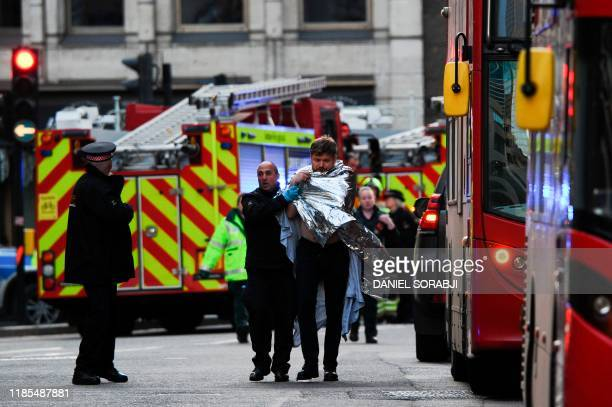 TOPSHOT Police assist an injured man near London Bridge in London on November 29 2019 after reports of shots being fired on London Bridge The...