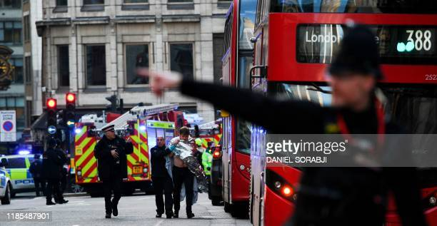 Police assist an injured man near London Bridge in London on November 29 2019 after reports of shots being fired on London Bridge The Metropolitan...