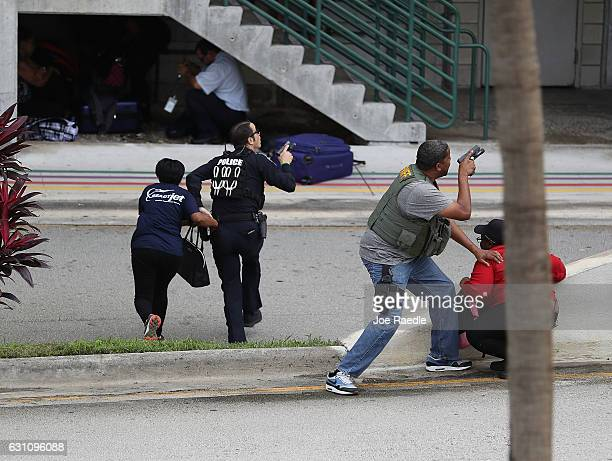 Police assist people seeking cover outside of Terminal 2 at Fort LauderdaleHollywood International airport after a shooting took place near the...