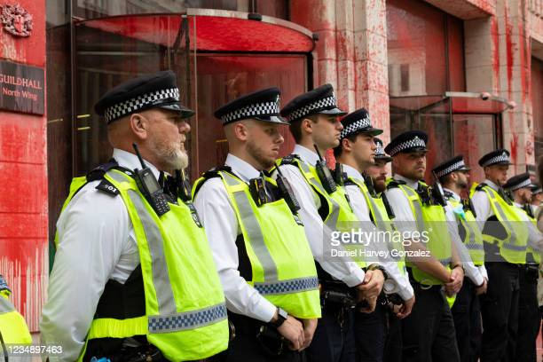 Police at an Extinction Rebellion protest line up in a row outside Guildhall, which has been covered in red paint to signify blood, on 27th August,...