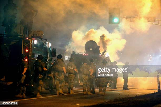 Police attempt to control demonstrators protesting the killing of teenager Michael Brown on August 18, 2014 in Ferguson, Missouri. Police shot smoke...