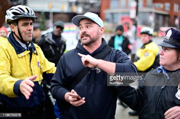 Police attempt to hold back a man reacting to a group of protestors outside the Army Navy game in Philadelphia PA on December 14 2019 Activist with...