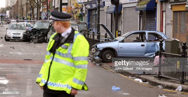 Police attend the scene in Bethnal Green Road east London after a black Mercedes fourwheel drive jeep being pursued by a police car crashed into...