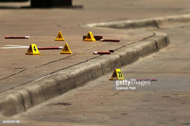 Police ballistic markers sit on the sidewalk in an area which is a crime investigation scene in downtown Dallas following the deaths of five police...
