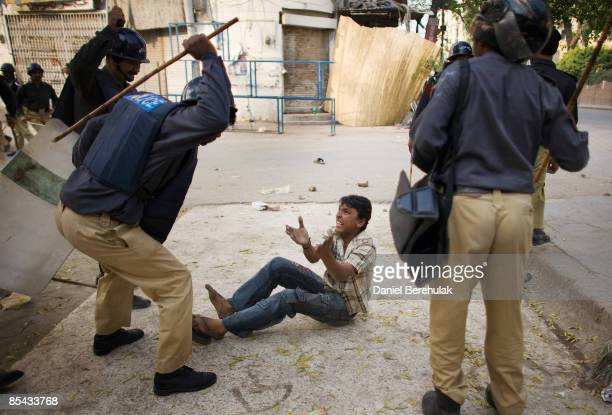 Police beat a boy suspected to be a protester on March 15, 2009 in Lahore, Pakistan. Violence erupted today after PML leader Nawaz Sharif, defied...