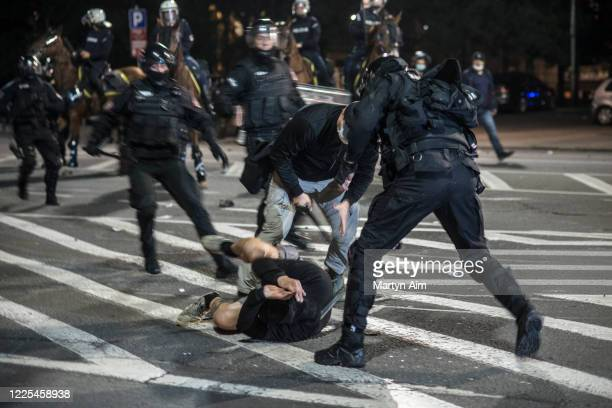 Police beat a protester as thousands of Serbians demonstrate outside parliament after the reintroduction of the coronavirus lockdown on July 7 2020...
