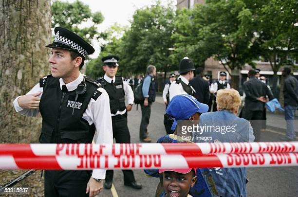 Police begin to allow residents back to their homes, July 29, 2005 in an apartment block where two suspected suicide bombers were arrested in west...