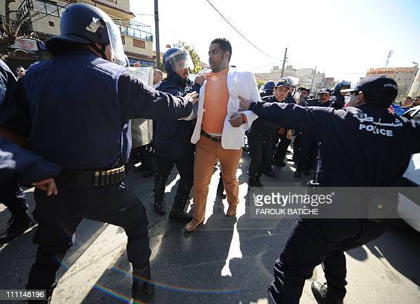 Police block a protestor on March 5 2011 in Algiers during a demonstration organized by the Rally for Culture and Democracy a splinter group of the...