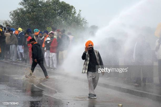 Police block a road and use a water cannon to disperse farmers marching to India's capital New Delhi to protest against the central government's...