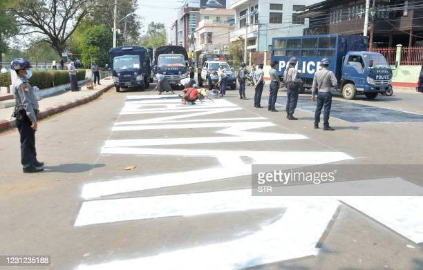 """Police block a road as workers remove protesters' graffiti with a message """"save Myanmar"""" during a demonstration against the military coup in..."""