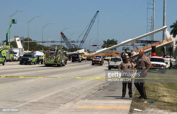 Police block a road near a newly installed pedestrian bridge that collapsed over a sixlane highway in Miami Florida on March 15 crushing a number of...
