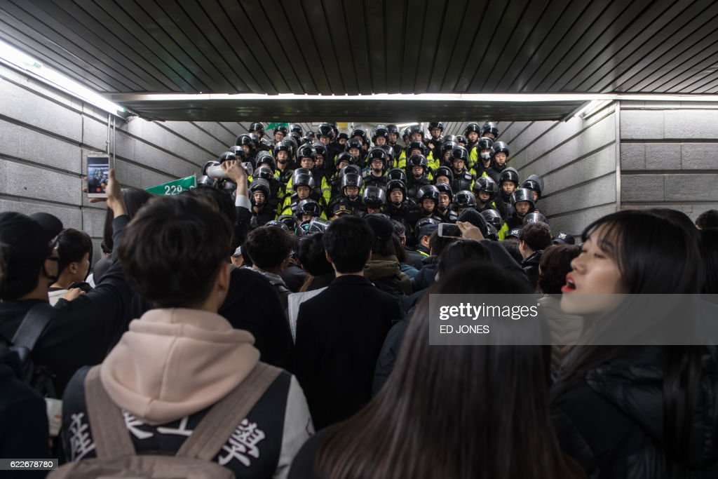 TOPSHOT - Police block a subway exit during anti-government protest in central Seoul on November 12, 2016. Up to one million people were expected to take to the streets of Seoul to demand the resignation of scandal-hit President Park Geun-Hye, in one of the largest anti-government protests in decades. / AFP PHOTO / Ed JONES