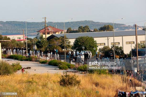 Police block an area where refugees and migrants from the destroyed Moria camp found shelter during an operation to move them in a new temporary camp...