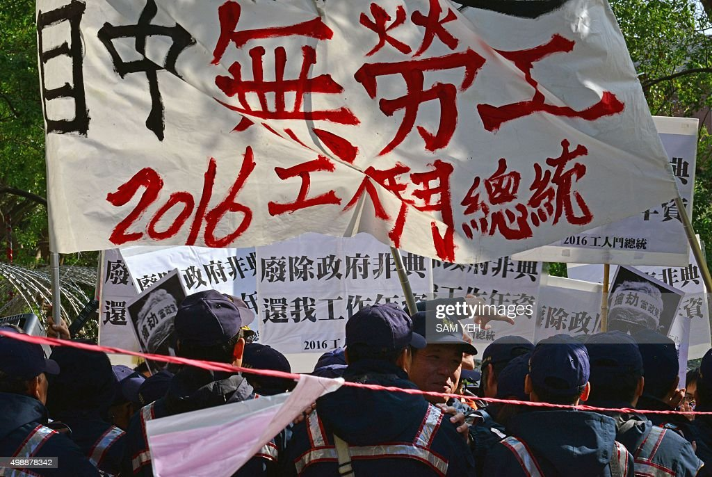 Police block off protesters (behind) from labour groups displaying a banners reading 'no labour in Tsai's mind' as Tsai Ing-wen, chairwoman of Taiwan's main opposition Democratic Progressive Party (DPP) and candidate for the presidential election, visits the Central Elections Commission to register in Taipei on November 27, 2015. Tsai will represent the DPP running in the Taiwan presidential election in January 2016. AFP PHOTO / Sam Yeh / AFP / SAM YEH