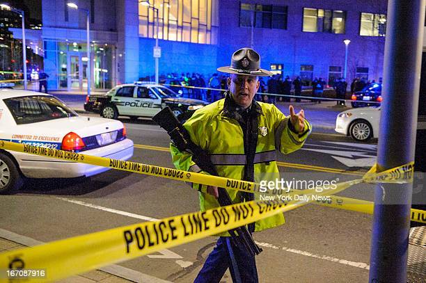 Police block road after a campus police officer at Massachusetts Institute of Technology was shot near Building 32 during hunt for two suspects in...