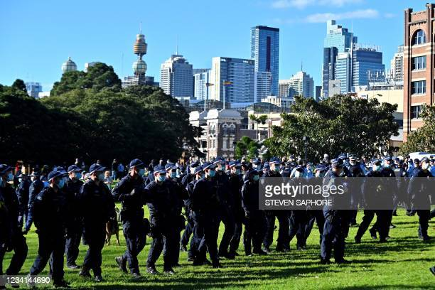 Police block the way to the marching protesters during an anti-lockdown rally in Sydney on July 24 as thousands of people gathered to demonstrate...