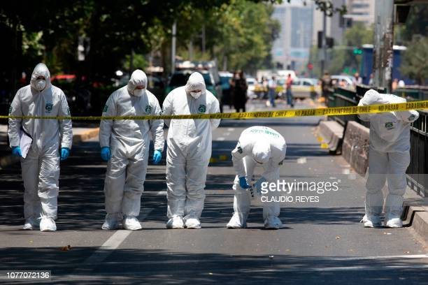 Police bomb squad personnel inspect the scene after a blast at a bus stop injured at least four people in downtown Santiago on January 4 2019 A...