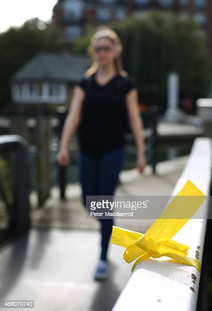 A police cadet reconstructs the last known movements of missing schoolgirl Alice Gross seen here walking past a yellow ribbon placed by friends and...