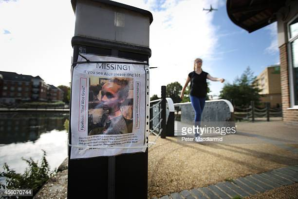 A police cadet reconstructs the last known movements of missing schoolgirl Alice Gross seen here walking past a missing poster placed by friends and...