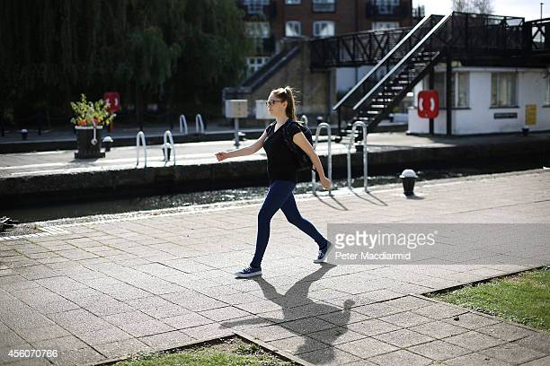 A police cadet reconstructs the last known movements of missing schoolgirl Alice Gross seen here walking at speed past Brentford Lock on September 25...