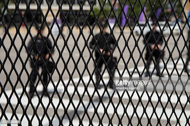 Police can be seen through the steel barricades surrounding the large secure area around the Quicken Loans Arena as antiTrump protestors march across...