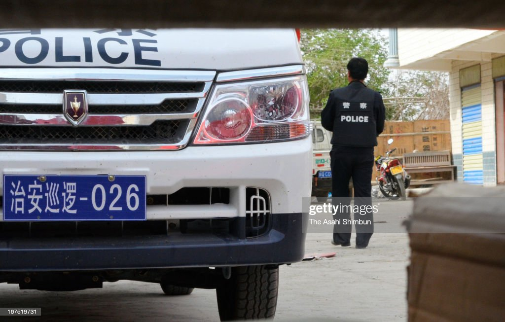 Police car and officers standing on guard at the house where armed clash broke off leaving 21 dead, amid ethnic tensions between the Muslim Uighur and Han Chinese communities on April 25, 2013 in Bachu, Xinjiang Uighur Autonomous Region, China.