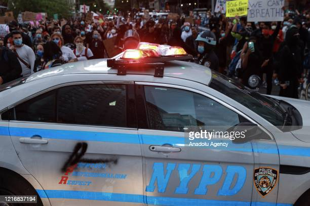 Police car blocking the road during a protest over the death of George Floyd, an unarmed black man who died after being pinned down by a white police...