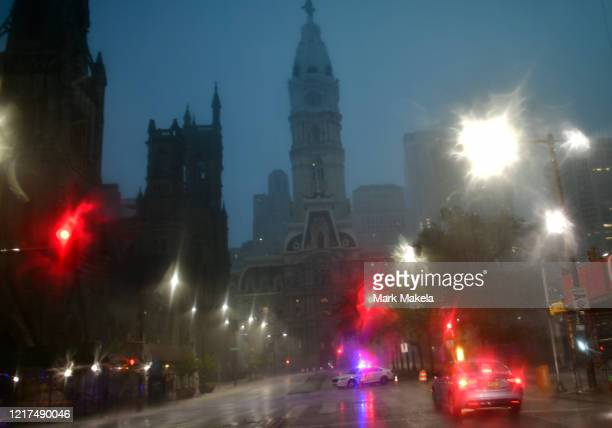 A police car blocks traffic towards City Hall during a downpour after a 6pm imposed curfew on June 3 2020 in Philadelphia Pennsylvania Protests...