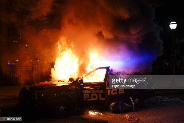 A police car burns during a protest on May 29 2020 in Atlanta Georgia Demonstrations are being held across the US after George Floyd died in police...