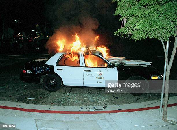 A police car burns during riots outside the Staples Center June 19 2000 in Los Angeles CA after a victory celebration by LA Lakers fans turned...