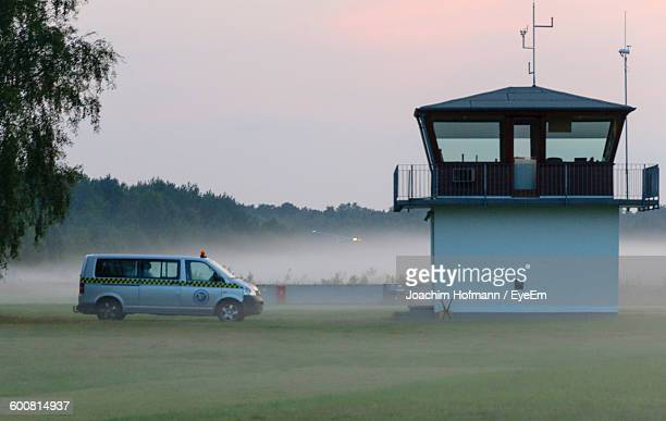 Police Car By Control Tower In Foggy Weather