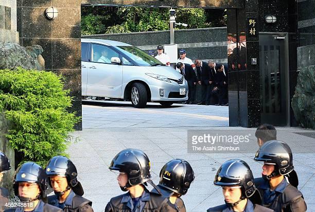 A police car carrying Kudokai leader Satoru Nomura leaves his home while members of Kudokai yakuza bow toward their boss on September 11 2014 in...
