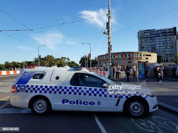 A police car cordons off the street as emergency personnel work at the scene of where a car ran over pedestrians in Flinders Street in Melbourne on...
