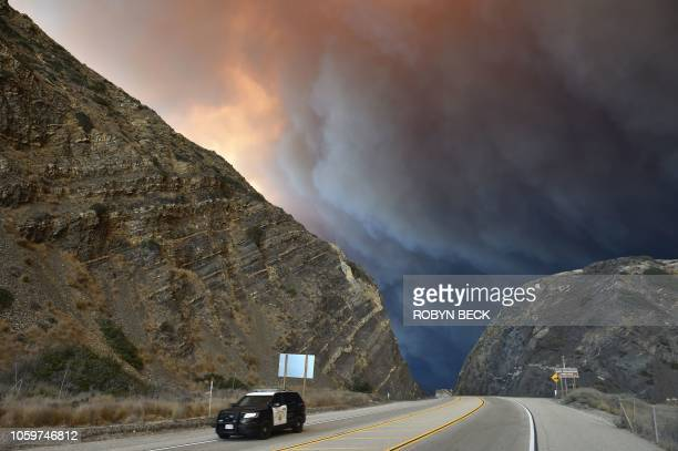 Police car drives beneath the smoke from the Woolsey Fire in Malibu, California, November 9, 2018. - About 75,000 homes have been evacuated in Los...