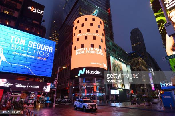 Police car drives near The Nasdaq in Times Square as people remain at home to stop the spread of coronavirus on March 29, 2020 in New York City....