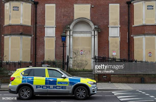 Police car drives past a closed and boarded up police station in Hackney as extra police officers have been deployed after a recent rise in killings...