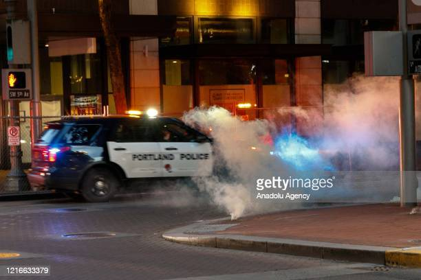 Police car drives through a cloud of tear gas while dispersing demonstrators gathered over the death of George Floyd an unarmed black man who died...