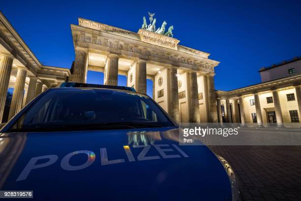 police car in front of the brandenburger tor (brandenburg gate) - (berlin, germany) - german culture stock pictures, royalty-free photos & images